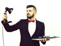 L'uomo d'affari o il presentatore del progetto tiene la lampada ed il computer portatile neri fotografie stock