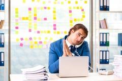 L'uomo d'affari occupato che lavora nell'ufficio immagini stock