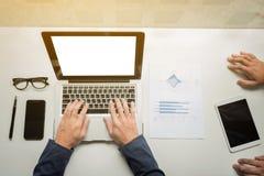 L'uomo d'affari passa il lavoro con il computer digitale della compressa ed astuto immagini stock