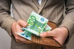 L'uomo d'affari passa il portafoglio della tenuta con la pila di soldi Fotografie Stock Libere da Diritti