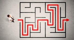 L'uomo d'affari perso ha trovato il modo in labirinto con la freccia rossa Fotografie Stock Libere da Diritti