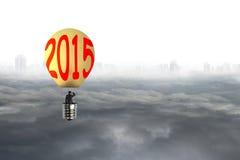 L'uomo d'affari prende a 2015 la mongolfiera a forma di lampadina con paesaggio urbano Fotografia Stock