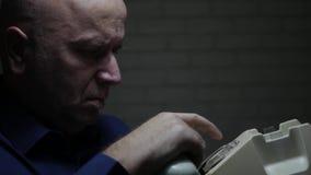 L'uomo d'affari preoccupato e serio compone un numero di telefono facendo uso di vecchio telefono video d archivio