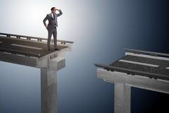 L'uomo d'affari pronto a sormontare il ponte rotto immagini stock libere da diritti