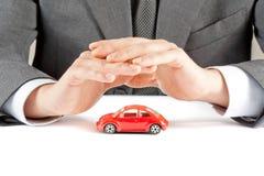 L'uomo d'affari protegge con le sue mani un'automobile rossa, concetto per assicurazione, acquisto, affittare, combustibile o serv Fotografia Stock