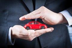 L'uomo d'affari protegge con le sue mani un'automobile rossa, concetto per assicurazione, acquisto, affittare, combustibile o serv Fotografie Stock