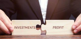 L'uomo d'affari raccoglie i puzzle con gli investimenti ed il profitto di parole Ritorno su investimento e capitale investito Tas fotografie stock