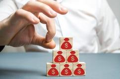 L'uomo d'affari rimuove un cubo con un'immagine dei dollari Concetto di fallimento Recessione economica Crisi finanziaria uscita  immagine stock libera da diritti