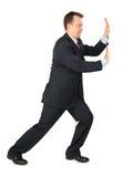 L'uomo d'affari riposa le mani contro la parete fotografia stock