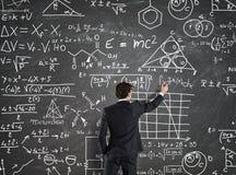 L'uomo d'affari risolve i problemi con i calcoli di per la matematica fotografia stock libera da diritti