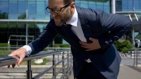 L'uomo d'affari ritiene improvvisamente il forte dolore in stomaco, sintomi di intossicazione alimentare immagine stock