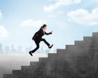 L'uomo d'affari salta all'più alta scala Immagini Stock