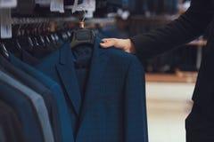 L'uomo d'affari sceglie il rivestimento di affari fra i vestiti che appendono sui ganci in negozio di vestiti Immagine Stock