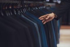 L'uomo d'affari sceglie il rivestimento di affari fra i vestiti che appendono sui ganci in negozio di vestiti Fotografie Stock Libere da Diritti