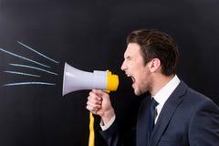 L'uomo d'affari scontroso sta urlando con l'altoparlante Fotografia Stock Libera da Diritti