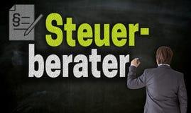 L'uomo d'affari scrive con gesso Stuerberater nel consulente fiscale tedesco sulla lavagna immagine stock