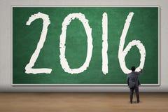 L'uomo d'affari scrive i numeri 2016 sulla lavagna Fotografia Stock