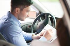 L'uomo d'affari scrive in sua nuova automobile Fotografia Stock Libera da Diritti