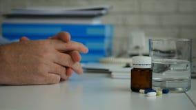 L'uomo d'affari Select e prende le pillole per un trattamento medico dalla Tabella immagini stock