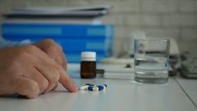 L'uomo d'affari Select e prende le pillole per un trattamento medico dalla Tabella immagine stock