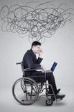 L'uomo d'affari sembra vertiginoso con il computer portatile e scribacchia Immagini Stock