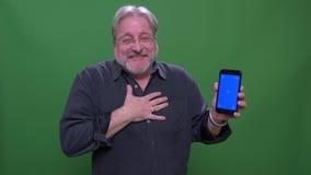 L'uomo d'affari senior mostra il pollice-su sullo schermo blu del telefono con il app isolato sul fondo verde di chromakey video d archivio