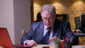 L'uomo d'affari senior nel funzionamento convenzionale del costume con il computer portatile ottiene distratto dallo smartphone i stock footage