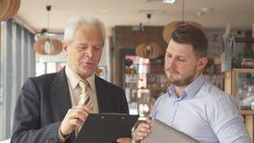 L'uomo d'affari senior spiega qualcosa sulla lavagna per appunti al suo partner fotografia stock
