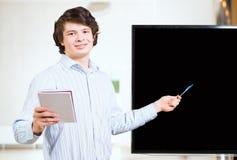 L'uomo d'affari senza formalità vestito mostra lo schermo in bianco immagine stock