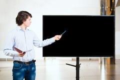 L'uomo d'affari senza formalità vestito mostra lo schermo in bianco immagini stock