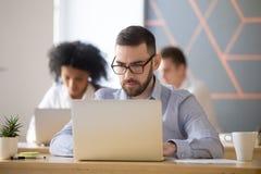 L'uomo d'affari serio ha messo a fuoco sul lavoro online del computer nel coworking immagine stock libera da diritti