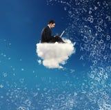L'uomo d'affari si è collegato con il suo computer portatile sopra una nuvola concetto della rete sociale e della dipendenza da I Immagine Stock