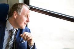 L'uomo d'affari si è sorpreso che cosa vede attraverso a finestra Immagine Stock