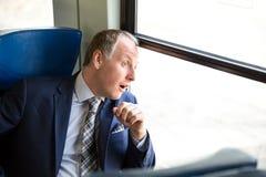 L'uomo d'affari si è sorpreso che cosa vede attraverso a finestra Immagine Stock Libera da Diritti