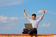 L'uomo d'affari si siede e celebra con il computer portatile esterno Fotografia Stock