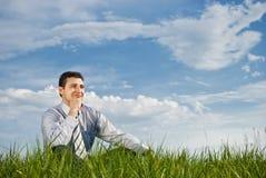 L'uomo d'affari si siede su erba Fotografie Stock Libere da Diritti