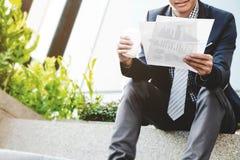 L'uomo d'affari si siedono e la risorsa di dati della lettura all'aperto con caffè fotografia stock