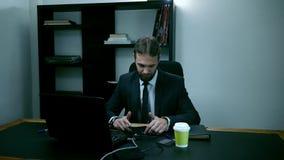 L'uomo d'affari sollecitato che si siede nell'ufficio dietro il computer portatile, lavoratore maschio esamina il telefono e si a video d archivio