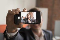 L'uomo d'affari sorridente fa l'immagine dell'autoritratto in ufficio immagini stock libere da diritti