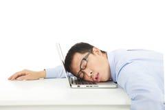 L'uomo d'affari sovraccarico stanco dorme sul computer portatile Fotografie Stock Libere da Diritti