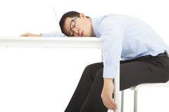 L'uomo d'affari sovraccarico stanco dorme sullo scrittorio immagini stock