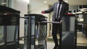 L'uomo d'affari sta attraversando un cancello girevole stock footage