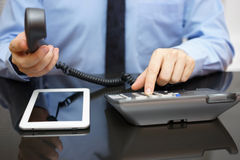 L'uomo d'affari sta chiamando il supporto quando legge il rapporto su COM della compressa fotografia stock