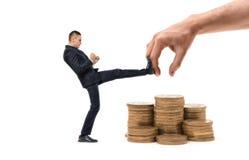 L'uomo d'affari sta colpendo con la mano enorme della gamba che prova ad afferrare il suo profitto Immagini Stock
