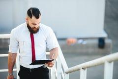 L'uomo d'affari sta con i documenti a disposizione fotografie stock