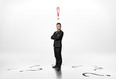 L'uomo d'affari sta con il punto esclamativo sopra lui e le domande sul pavimento Immagine Stock