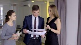L'uomo d'affari sta dando consiglia circa gli investimenti alla donna di affari ed il suo segretario femminile sta prendendo le n stock footage