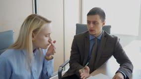 L'uomo d'affari sta dando le risposte al giovane responsabile femminile nel suo ufficio video d archivio