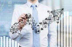 L'uomo d'affari sta disegnando una freccia crescente sullo schermo di vetro Icone di affari come parte integrante del grafico cre Fotografie Stock