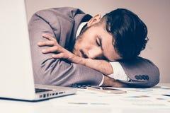 L'uomo d'affari sta dormendo sullo scrittorio Fotografia Stock